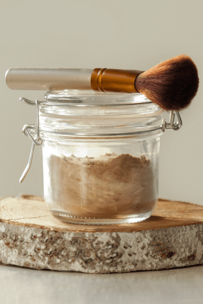 Jar of dry shampoo with brush to apply it