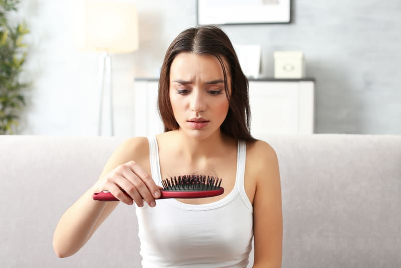 woman with hairbrush full of hair from hair loss