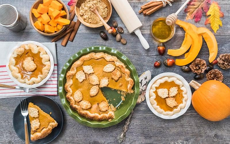 Fresh pumpkin, pumpkin pie and baking goods on a table