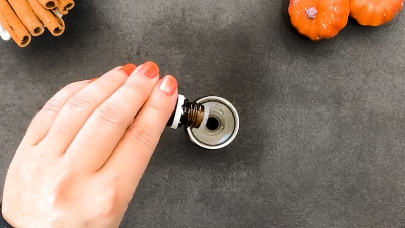 Pour essential oils into glass bottle of diy pumpkin spice essential oil room spray
