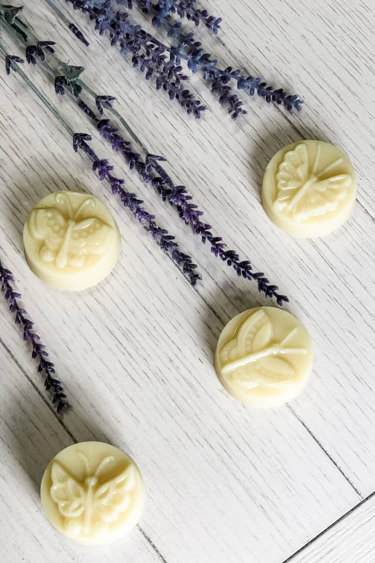 4 butterfly lotion bars on white table with lavender plants
