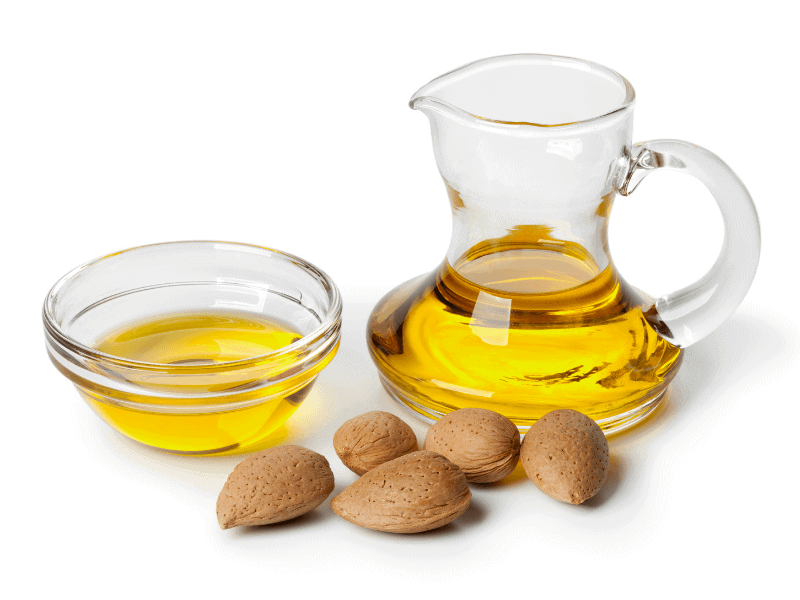 Almond oil in pitcher and bowl with almonds