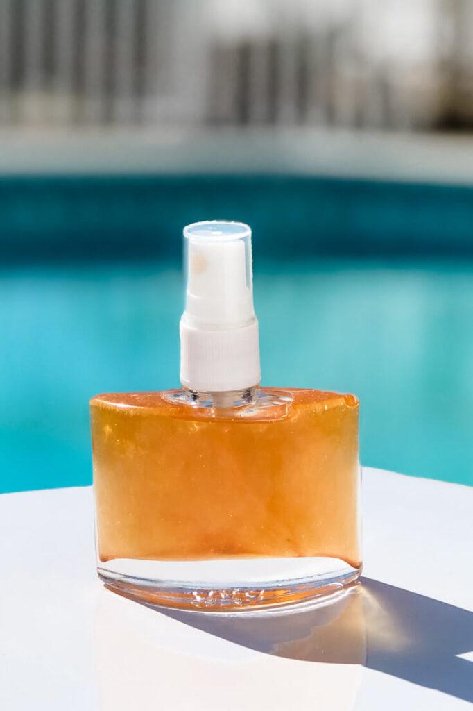 Spray bottle of diy shimmer body oil on table